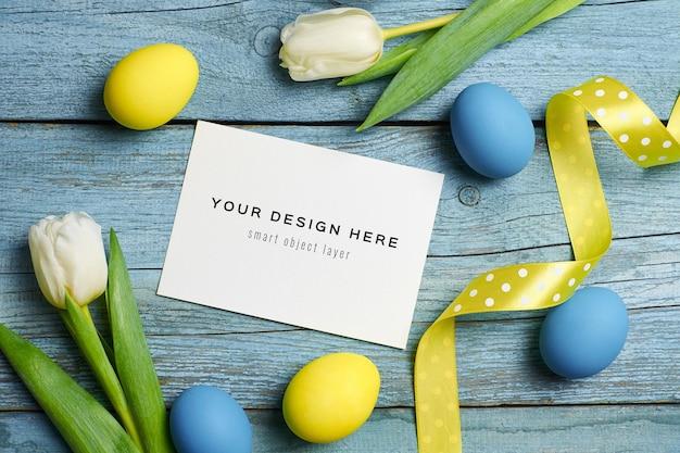 Maquette de carte de voeux de vacances de pâques avec des oeufs colorés et des fleurs de tulipes