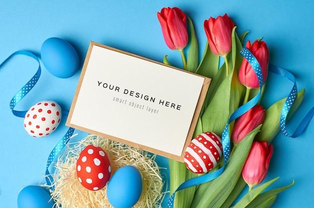 Maquette de carte de voeux de vacances de pâques avec des oeufs colorés, des rubans et des fleurs de tulipes rouges sur bleu