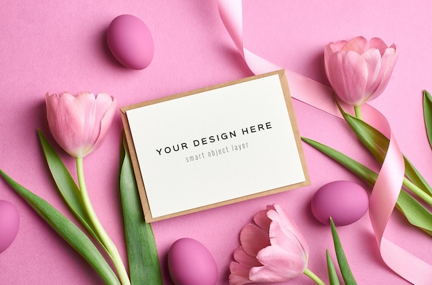 Maquette de carte de voeux de vacances de pâques avec des oeufs colorés et des tulipes