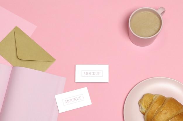 Maquette cartes de visite sur une table rose avec une tasse et un gâteau