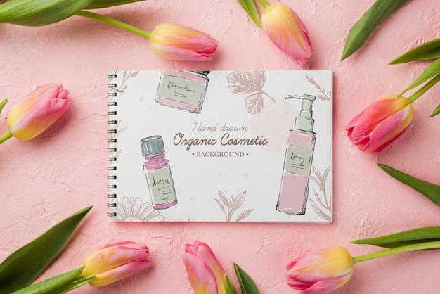 Maquette de cosmétiques vue de dessus avec des fleurs