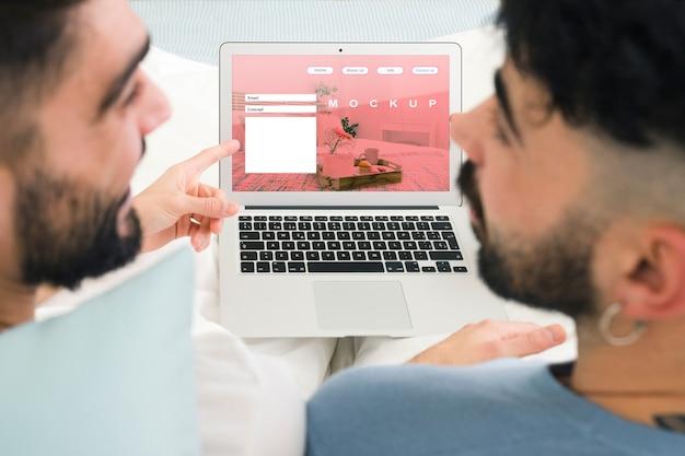 Maquette de couple gay et d'ordinateur portable