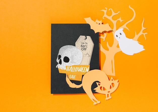 Maquette de couverture d'halloween avec des éléments coupés en papier