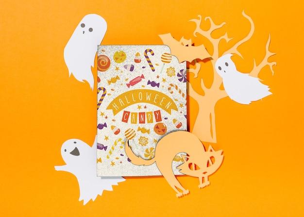 Maquette de couverture d'halloween avec des fantômes coupés en papier et un chat