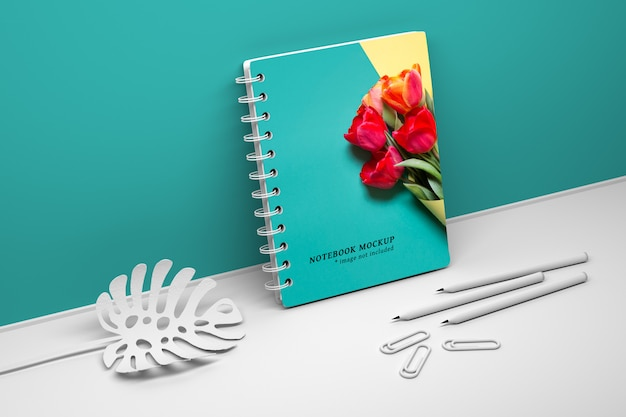 Maquette de couverture modifiable avec cahier à spirale, crayons et plante monstera