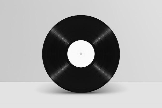Maquette de disque vinyle vierge, vue de face, debout contre un mur blanc
