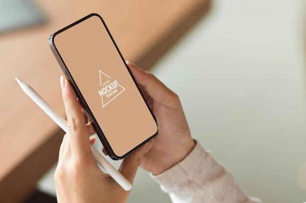 Maquette d'écran mobile vierge tout en tenant un stylet avec un arrière-plan flou