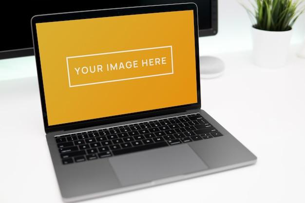 Maquette d'écran d'ordinateur portable sur un bureau blanc au bureau à domicile