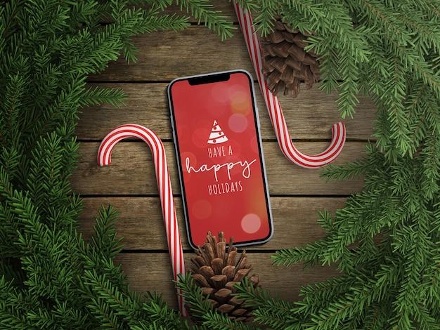 Maquette d'écran de téléphone avec décoration de guirlande de noël et canne à sucette
