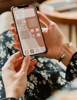 Maquette d'écran de téléphone psd avec main tenant dans des widgets beiges esthétiques