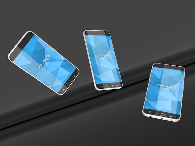 Maquette d'écrans de smartphone en lévitation dans un studio noir réfléchissant