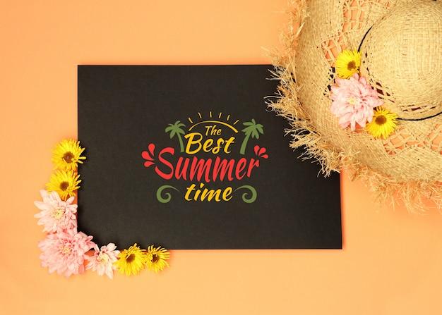 Maquette d'été noire avec chapeau de paille et fleurs