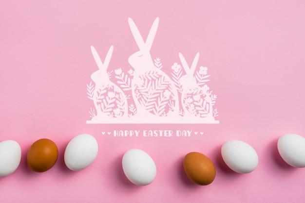 Maquette de fond rose avec des oeufs de pâques et des lapins