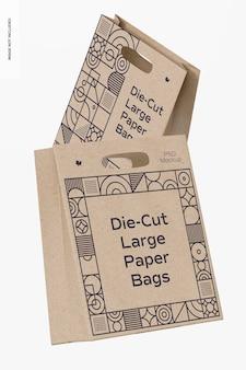 Maquette de grands sacs en papier découpés à l'emporte-pièce, flottant