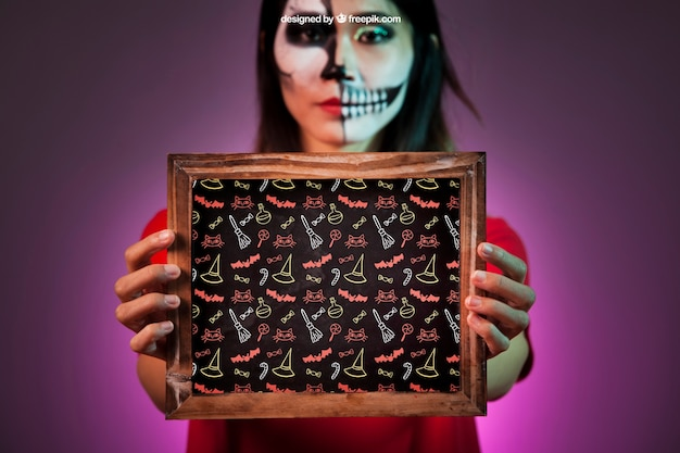 Maquette d'halloween avec une femme tenant l'ardoise dans les mains