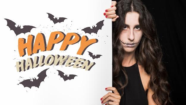 Maquette d'halloween avec lettrage sur grand tableau et femme