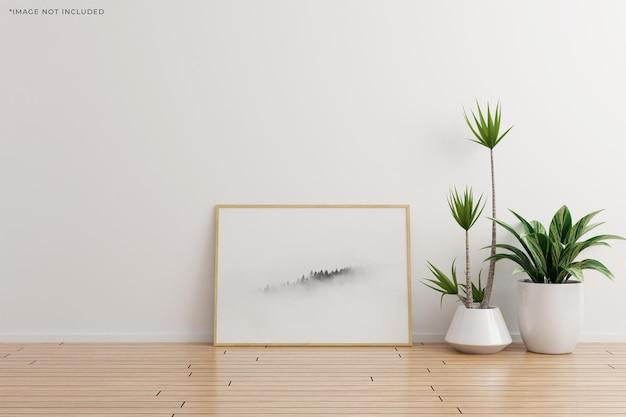 Maquette horizontale de cadre photo en bois sur une pièce vide de mur blanc avec des plantes sur un plancher en bois