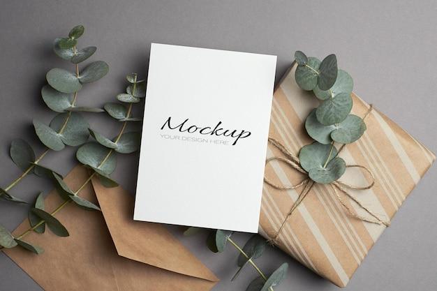 Maquette d'invitation ou de carte de voeux avec boîte-cadeau et brindilles d'eucalyptus fraîches sur fond gris