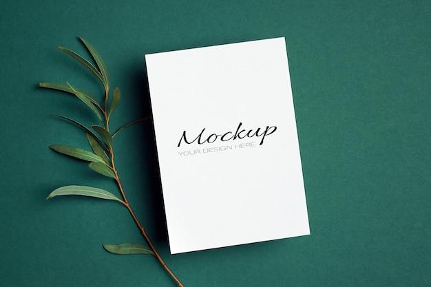 Maquette d'invitation ou de carte de voeux avec brindille d'eucalyptus sur vert