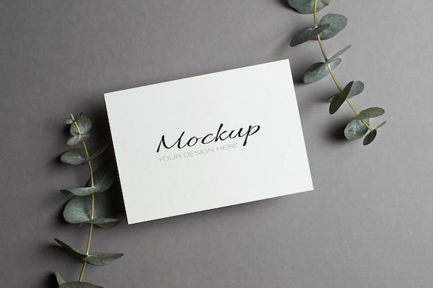 Maquette d'invitation ou de carte de voeux avec des brindilles d'eucalyptus sur gris