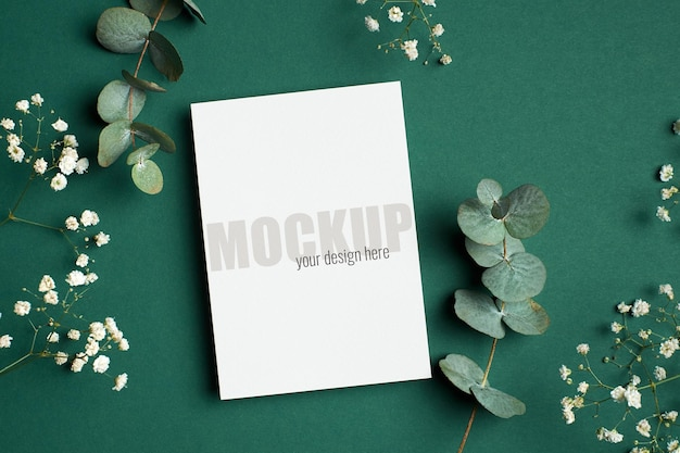 Maquette d'invitation ou de carte de voeux avec des brindilles d'eucalyptus et d'hypsophile sur vert