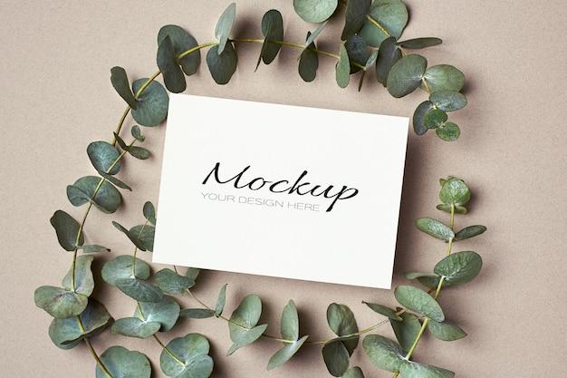 Maquette d'invitation ou de carte de voeux avec des brindilles d'eucalyptus vertes