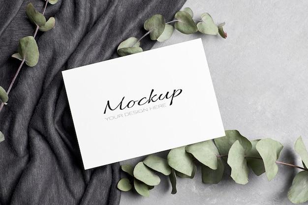 Maquette d'invitation ou de carte de voeux avec des brindilles d'eucalyptus