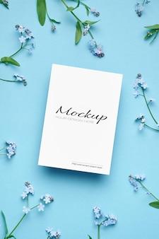 Maquette d'invitation ou de carte de voeux avec des brindilles de fleurs de cerisier de printemps sur bleu