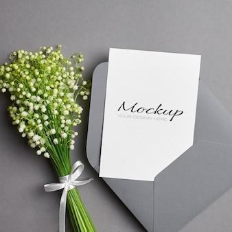 Maquette d'invitation ou de carte de voeux avec enveloppe et bouquet de fleurs de muguet