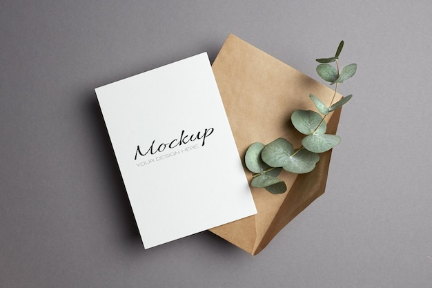 Maquette d'invitation ou de carte de voeux avec enveloppe et brindille d'eucalyptus sur gris