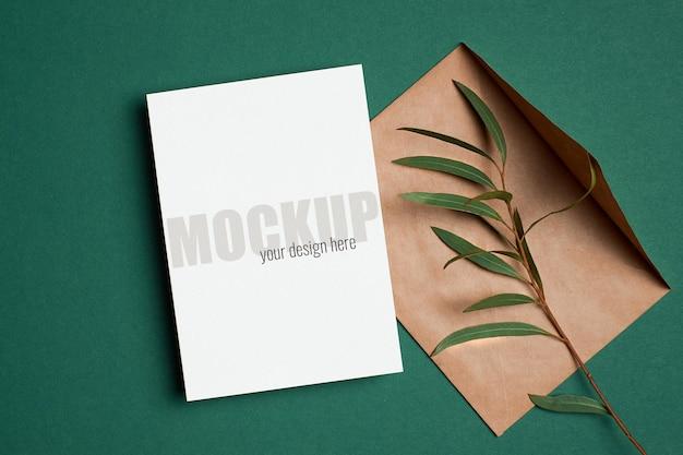 Maquette d'invitation ou de carte de voeux avec enveloppe et brindille d'eucalyptus sur vert
