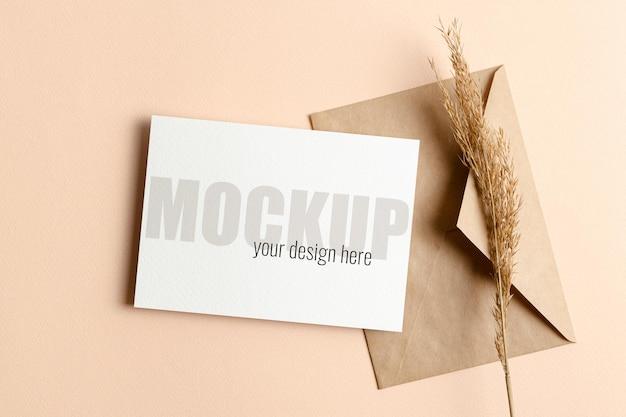 Maquette d'invitation ou de carte de voeux avec enveloppe et décorations de plantes sèches