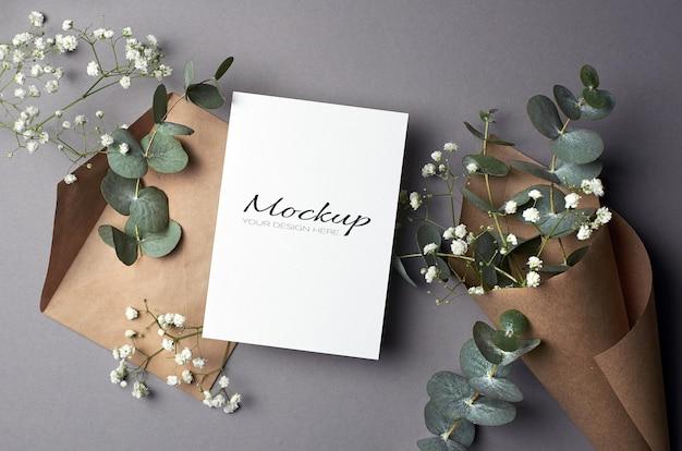 Maquette d'invitation ou de carte de voeux avec enveloppe et fleurs d'eucalyptus et d'hypsophile