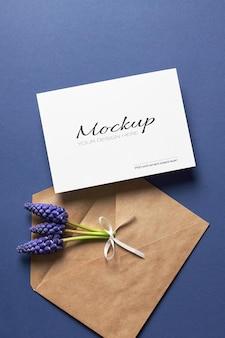 Maquette d'invitation ou de carte de voeux avec enveloppe et fleurs de muscari bleu de printemps