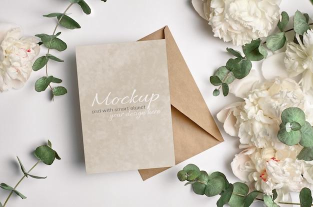 Maquette d'invitation ou de carte de voeux avec enveloppe et fleurs de pivoine blanches avec des brindilles d'eucalyptus