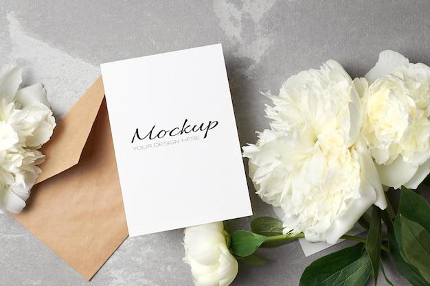 Maquette d'invitation ou de carte de voeux avec enveloppe et fleurs de pivoine blanches sur fond gris