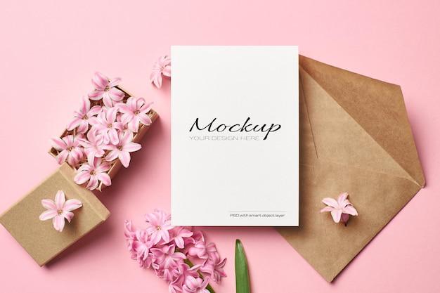 Maquette d'invitation ou de carte de voeux avec enveloppe et fleurs roses en boîte