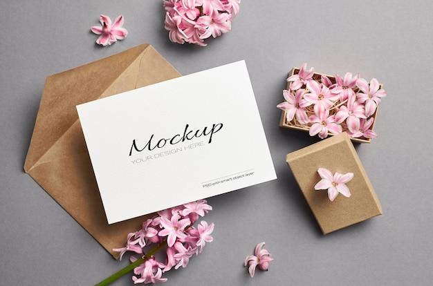 Maquette d'invitation ou de carte de voeux avec enveloppe et fleurs roses de printemps dans une boîte