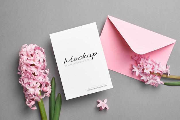 Maquette D'invitation Ou De Carte De Voeux Avec Enveloppe Rose Et Fleurs De Jacinthe Sur Fond Gris PSD Premium