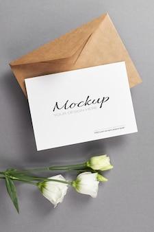 Maquette d'invitation ou de carte de voeux avec des fleurs d'eustoma blanches sur fond gris