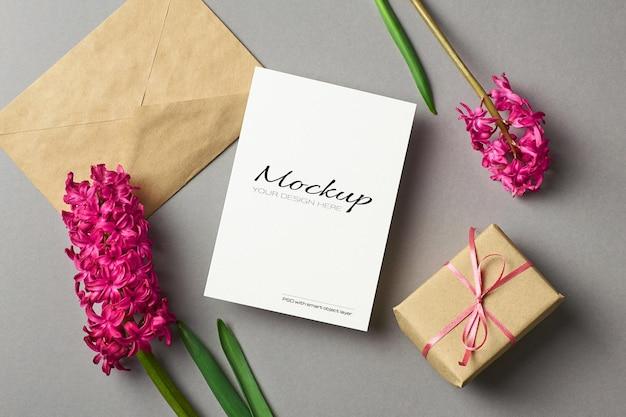 Maquette d'invitation ou de carte de voeux avec des fleurs de jacinthe, une enveloppe et une boîte-cadeau