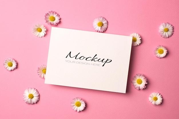 Maquette d'invitation ou de carte de voeux avec des fleurs de marguerite sur rose