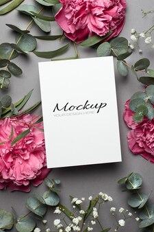 Maquette d'invitation ou de carte de voeux avec des fleurs de pivoine, des brindilles d'hypsophile et d'eucalyptus