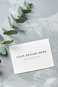 Maquette d'invitation de mariage avec des brindilles d'eucalyptus frais sur fond gris