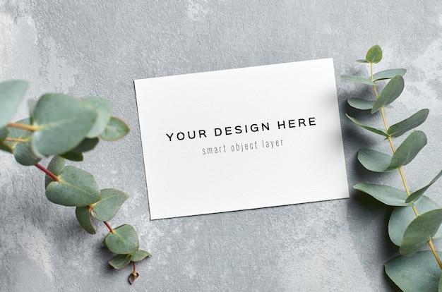 Maquette d'invitation de mariage avec des brindilles d'eucalyptus frais