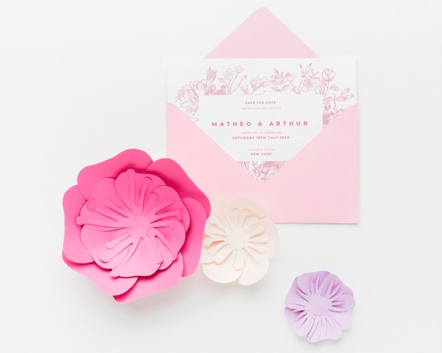 Maquette d'invitation de mariage avec des fleurs en papier sur fond blanc