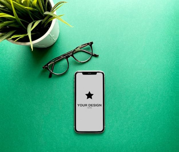 Maquette iphone 11 sur fond vert avec des plantes et des lunettes