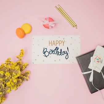 Maquette de joyeux anniversaire avec carte d'invitation et fleurs