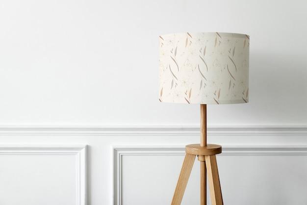 Maquette de lampe à motifs floraux psd sur un intérieur minimal de mur blanc