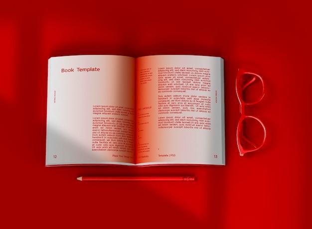 Maquette de livre à couverture rigide ouverte en 3d avec des lunettes et un crayon